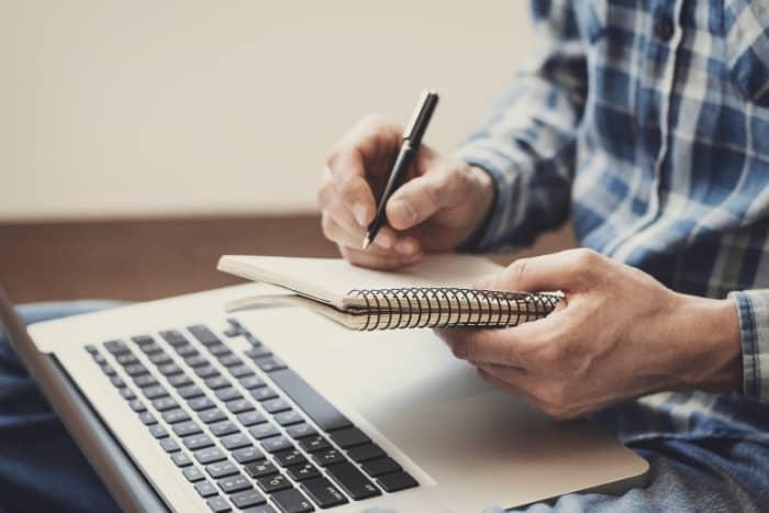 freelance writing job boards taking notes at laptop